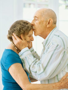 Side view of a senior man kissing a senior woman's forehead