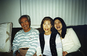 Emi Gusukuma and her parents Gus and Yuki sitting on the couch