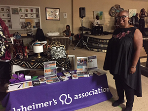 Teri Carlyle poses next to her Alzheimer's Association table at The Longest Day fundraising event