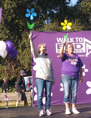 Laura McDermott raises a blue flower at Walk to End Alzheimer's