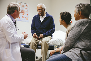 Doctor talking with a patient and his caregivers