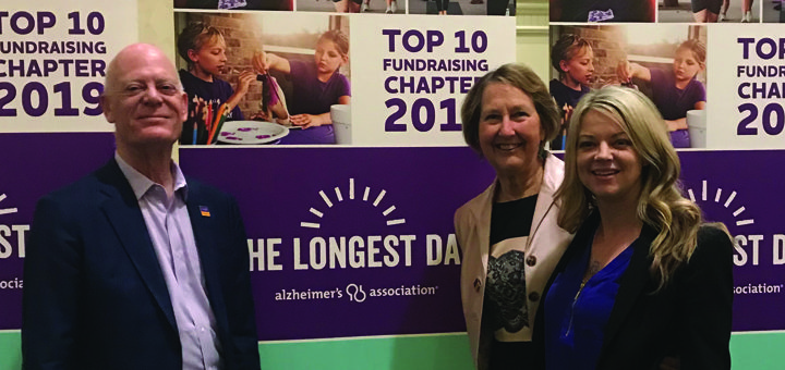 Kirsten Guanella poses with Bart and Nancy under The Longest Day Top 10 Banner