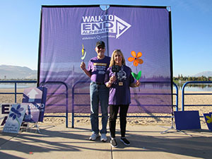 Nancy and husband hold flowers at Reno-Sparks Walk to End Alzheimer's in honor of her mother