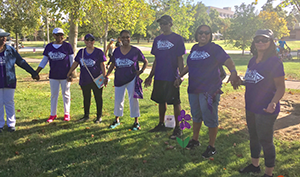 Saints for a Cure team holds hands under the oak tree during the Walk to End Alzheimer's