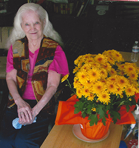 Margie, who had Alzheimer's, posing with some flowers