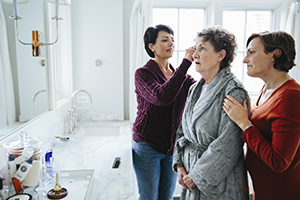 Daughters in the bathroom caring for their mother who has Alzheimer's