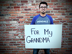 """Quincy participates in Walk to End Alzheimer's by holding a sign that says """"For my Grandma"""""""